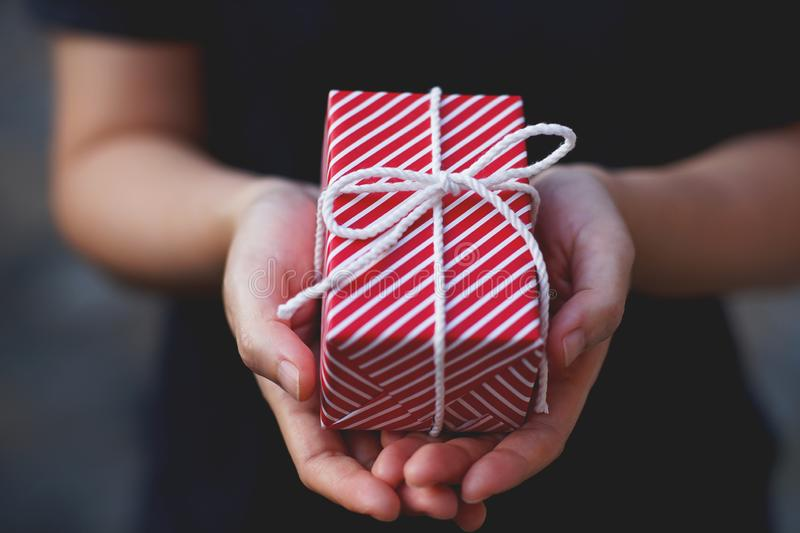 Lovely red gift box in hand, sweet valentine present giving concept. Copy space stock image