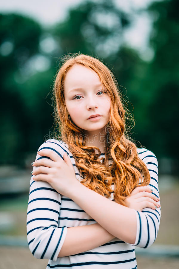 Lovely red-haired girl hugging herself and looking at camera royalty free stock photo
