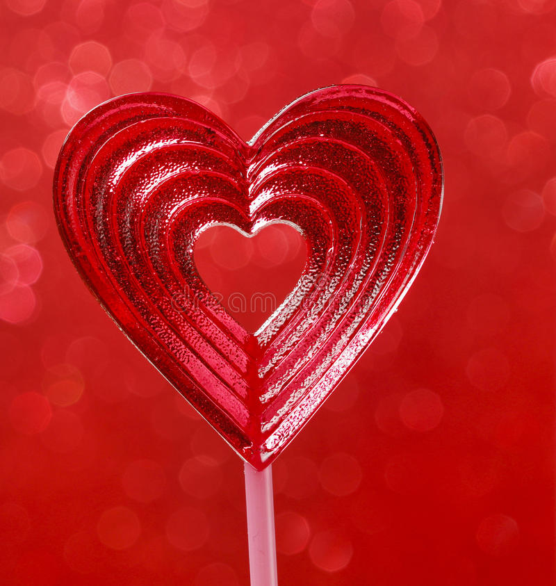 Lovely red lollipop in heart shape. Symbol of sweet love. Valentines day gift. Wooden background stock photography