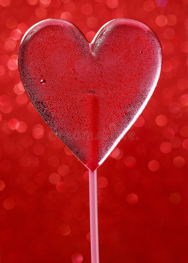 Lovely red lollipop in heart shape. Symbol of sweet love. Valentines day gift. Wooden background royalty free stock photo