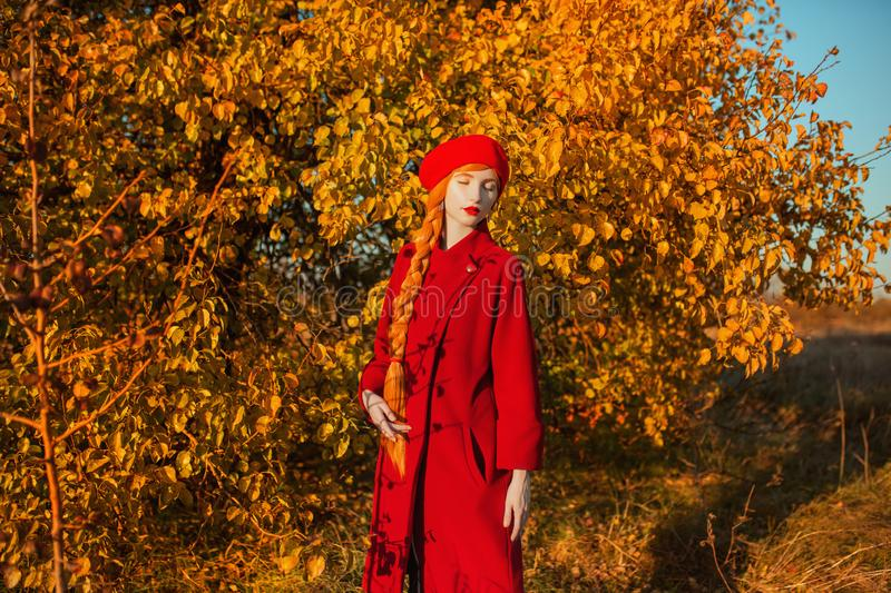Lovely redhead woman with long hair in red coat on autumn background. Redhead girl with long braided plait on background of forest. With orange autumn leaves stock images