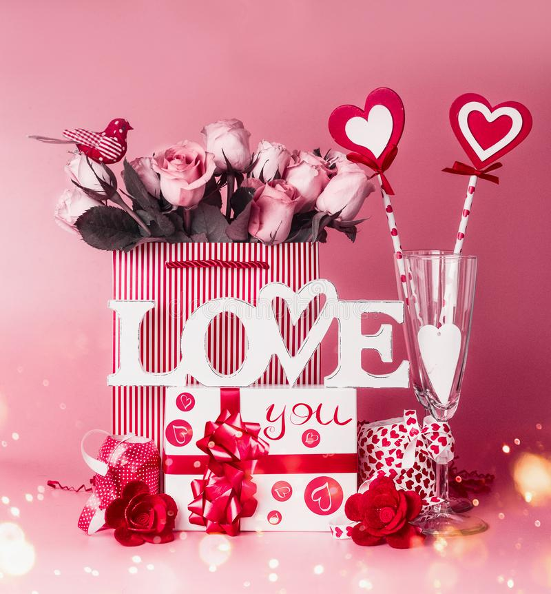 Lovely romantic composition for Valentines day. Love you message with gift box , red ribbons, bag with roses and hearts ,. Decoration and champagne glasses stock image