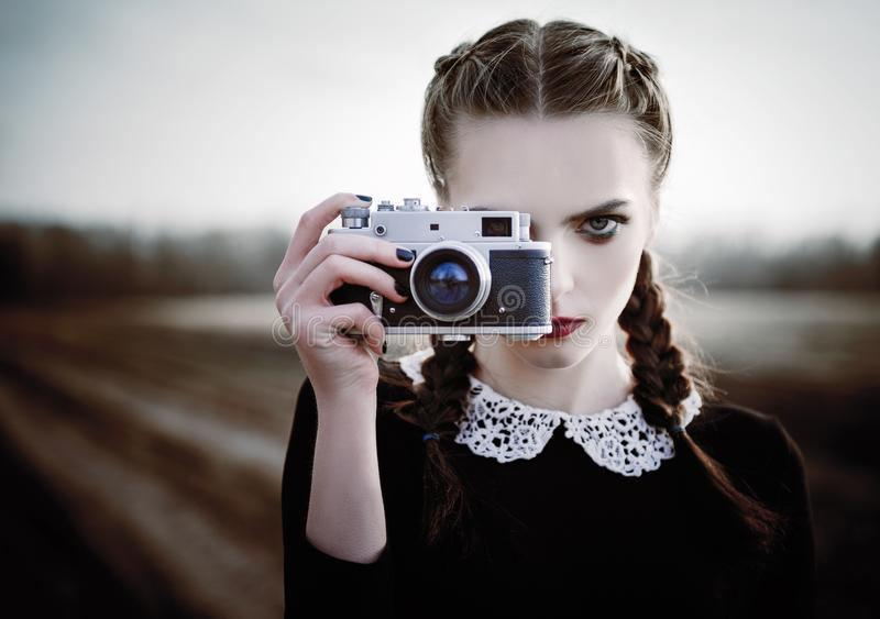 Lovely sad young girl photographing on vintage film camera. Closeup outdoor portrait. Lovely sad young girl photographing on the vintage film camera. Closeup royalty free stock photography
