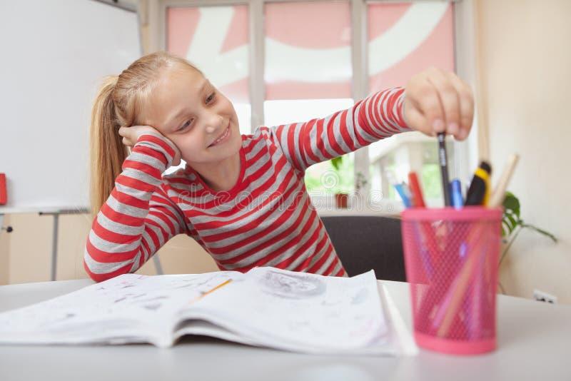 Lovely schoolgirl enjoying drawing stock image