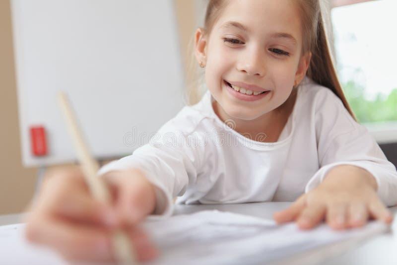 Lovely schoolgirl enjoying drawing royalty free stock photo