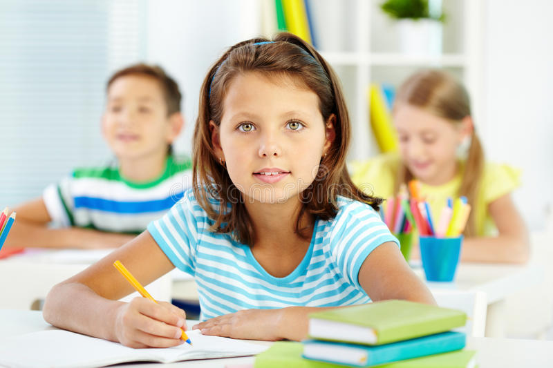 Lovely schoolgirl. Lovely girl being busy with acquiring knowledge stock image
