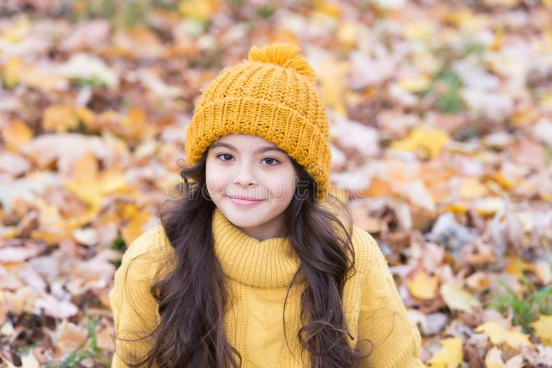 Lovely season. Keep warmest this autumn. Child in yellow hat outdoors. Autumn skin care routine. Kid wear warm knitted. Hat. Warm woolen accessory. Girl long royalty free stock photos