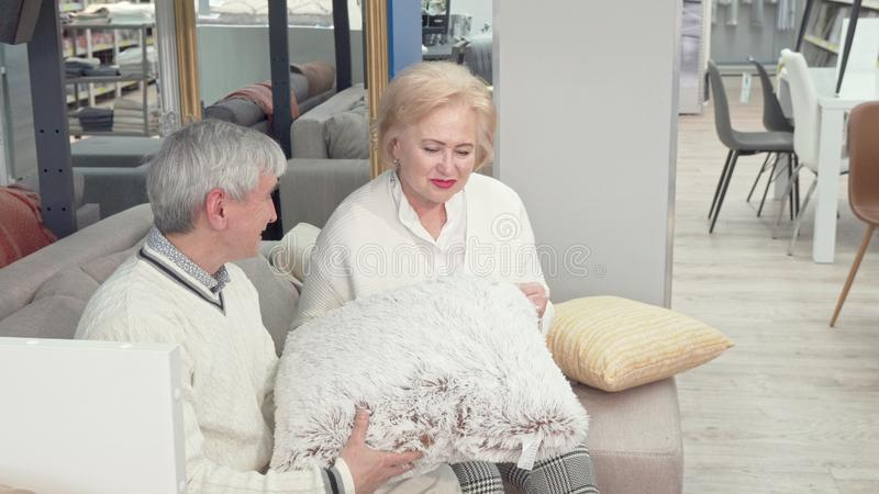 Lovely senior couple choosing new cushions at furniture store. Cheerful elderly women laughing, talking to her husband while shopping at furniture shop stock images