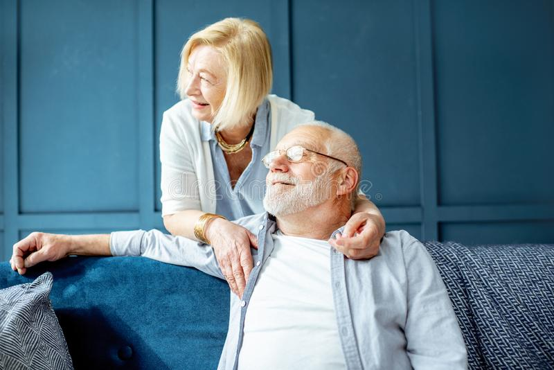 Lovely senior couple on the couch at home royalty free stock photos