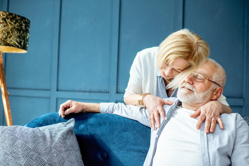 Lovely senior couple on the couch at home royalty free stock images
