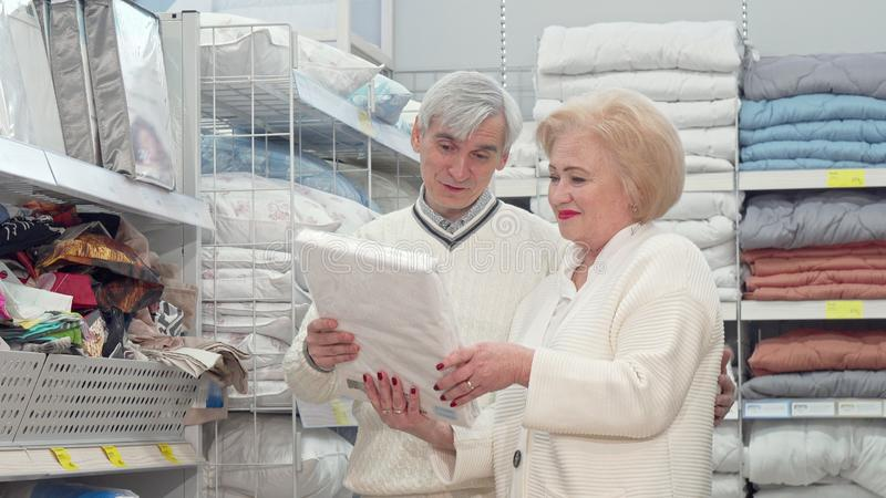 Lovely senior couple shopping for bed sheets at furniture store. Elderly husband and wife buying bedding at furnishings department shop. Senior husband and royalty free stock images