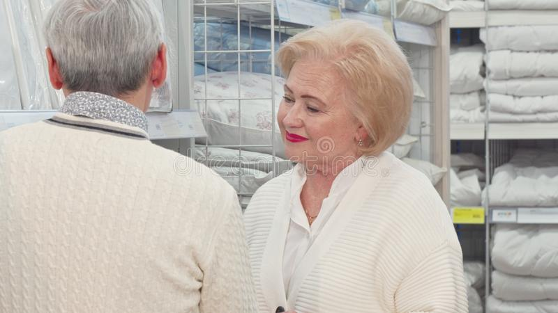 Lovely senior lady and her husband choosing linen for their home. Charming elderly female customer enjoying shopping for textile with her husband at royalty free stock photos
