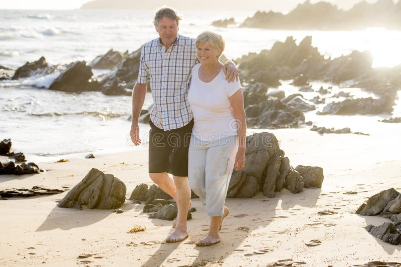 Lovely senior mature couple on their 60s or 70s retired walking happy and relaxed on beach sea shore in romantic aging together. And retirement husband and wife stock photos