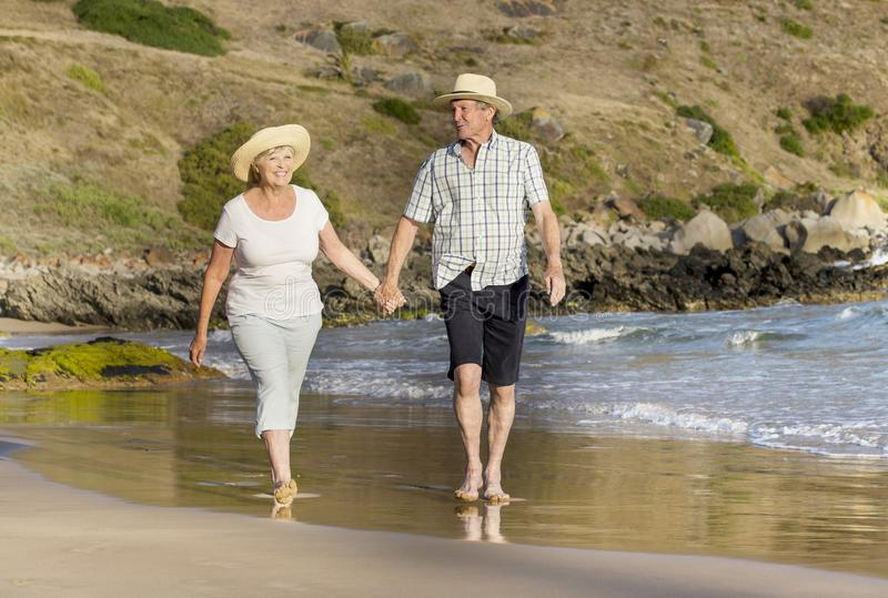 Lovely senior mature couple on their 60s or 70s retired walking happy and relaxed on beach sea shore in romantic aging together. And retirement husband and wife stock images