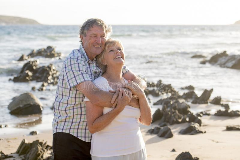Lovely senior mature couple on their 60s or 70s retired walking happy and relaxed on beach sea shore in romantic aging together. And retirement husband and wife royalty free stock photography