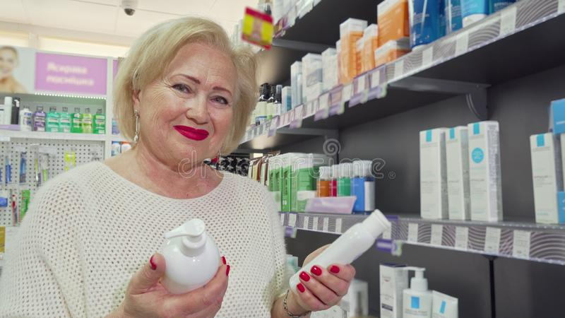 Lovely senior woman smiling, choosing between two products at the drugstore royalty free stock images