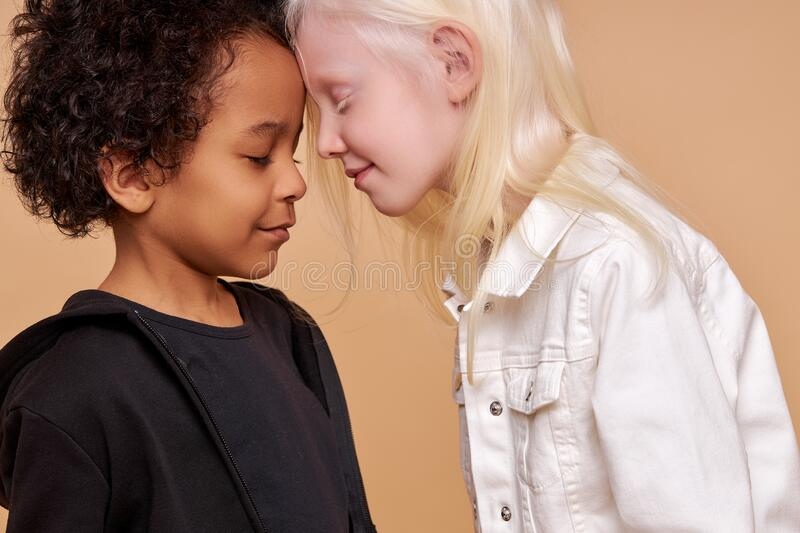 Lovely sensual albino girl going to kiss african black boy. Beautiful friednly children with unusual appearance stock photo