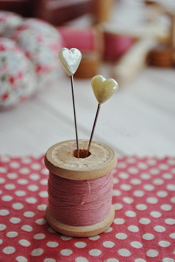 LOVELY SEWING TOOLS BACKGROUNDS. NEEDLES, BOBBIN, PINK POLKA DOT FABRIC, HEART PINS AGAINST WOODEN DESK royalty free stock image