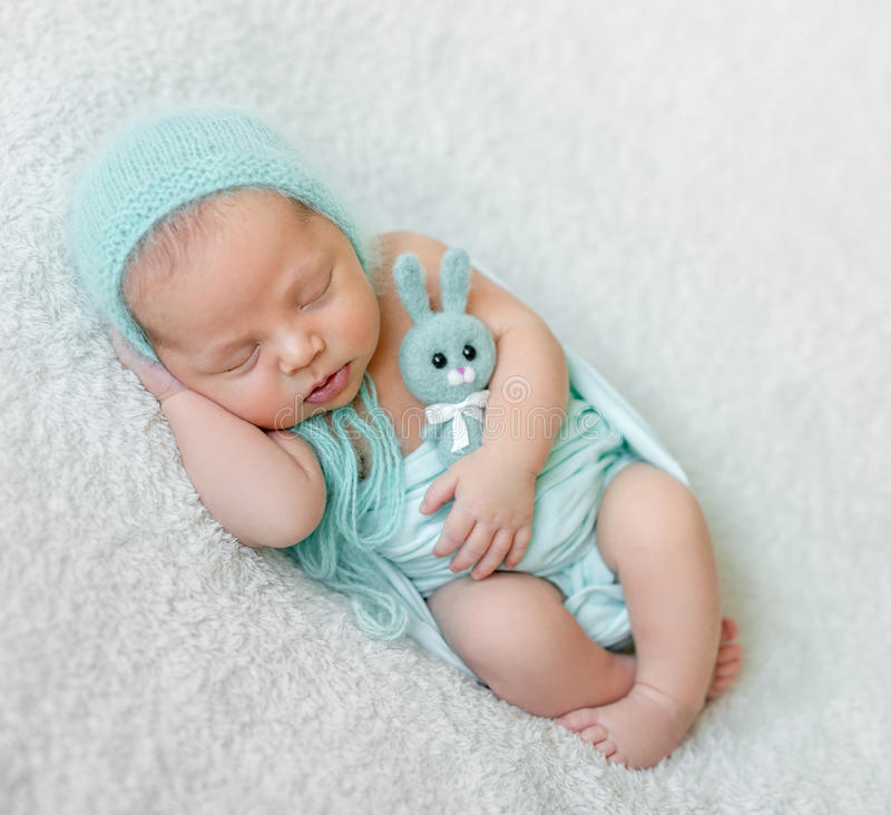 Lovely sleeping baby with blue hat, panties and toy. On white blanket royalty free stock photography