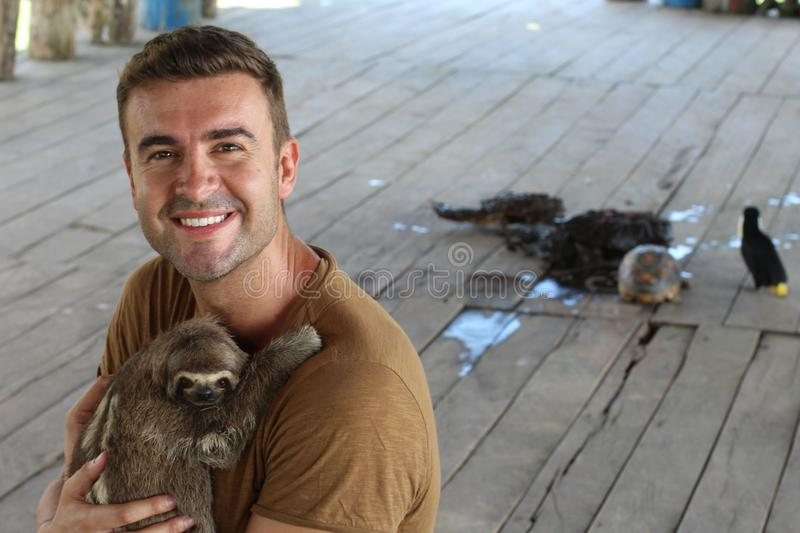 Lovely sloth hugging a man.  stock photos