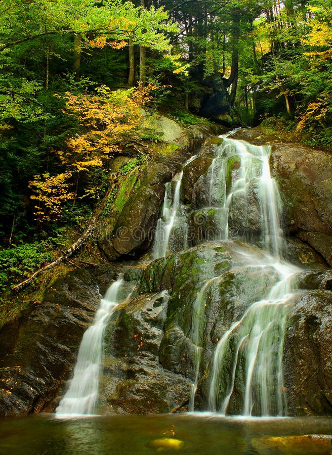Mountain Waterfall In Autumn. A lovely small waterfall cascades into a mountain river in early autumn in the Appalachians royalty free stock images