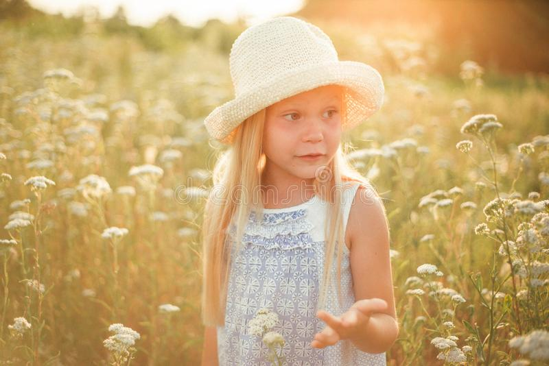 Lovely smiling blond girl in a field at sunset. Cute girl in a flowering field sniffs flowers. Ukrainian in a hat and dress near stock photos