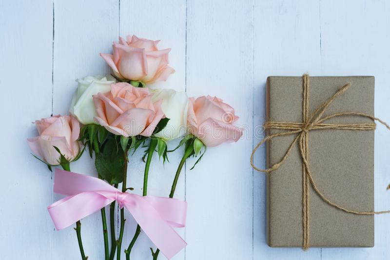 Lovely soft orange pink color rose tied by pink ribbon and brown gift box on white wood table background, sweet valentine present stock photography
