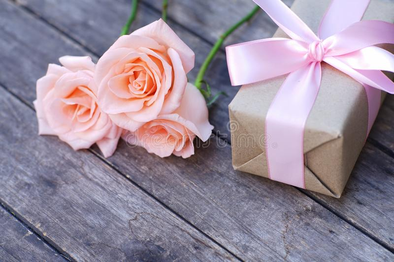 Lovely soft orange pink color rose tied by pink ribbon and brown gift box on wood table background, sweet valentine present stock photo