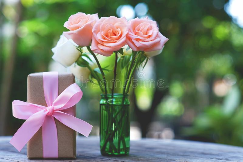 Lovely soft orange pink color rose tied by pink ribbon and brown gift box on white wood table background, sweet valentine present. Concept, copy space stock photography