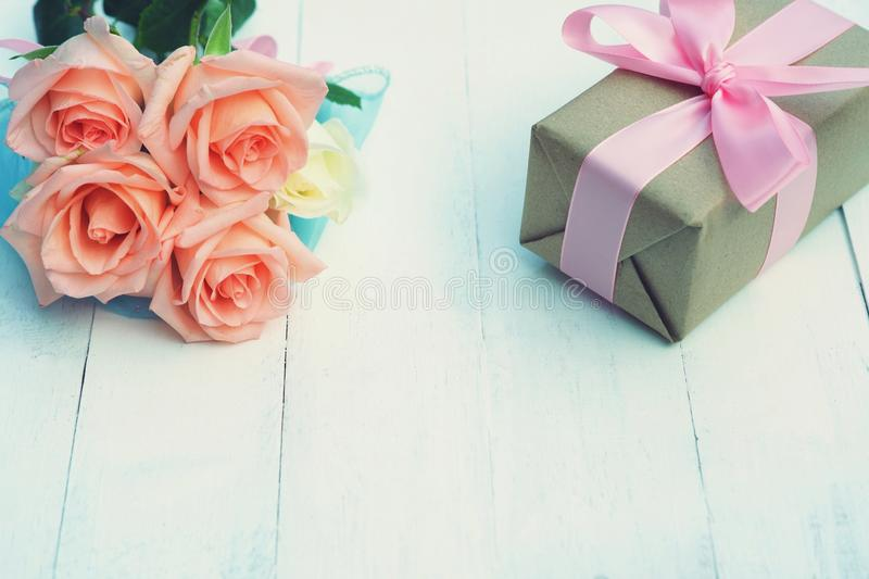 Lovely soft orange pink color rose tied by pink ribbon and brown gift box on white wood table background, sweet valentine present. Concept, copy space stock photos