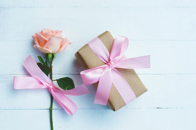 Lovely soft orange pink color rose tied by pink ribbon and brown gift box on white wood table background, sweet valentine present. Concept, copy space stock image