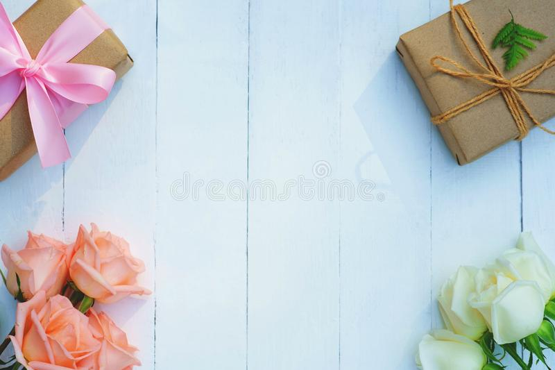 Lovely soft orange pink color rose tied by pink ribbon and brown gift box on white wood table background, sweet valentine present royalty free stock image