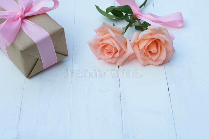 Lovely soft orange pink color rose tied by pink ribbon and brown gift box on white wood table background, sweet valentine present royalty free stock photography