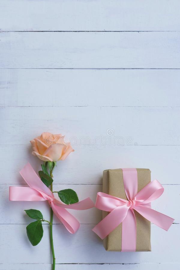 Lovely soft orange pink color rose tied by pink ribbon and brown gift box on white wood table background, sweet valentine present stock photo