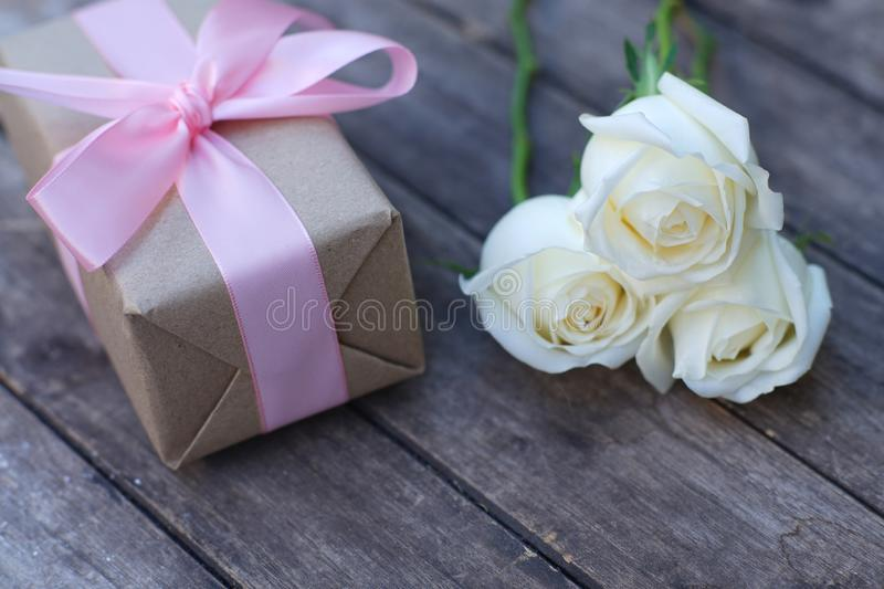 Lovely soft orange white color rose tied by pink ribbon and brown gift box on wood table background, sweet valentine present. Concept, copy space stock photo