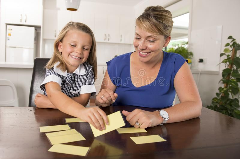 Lovely sweet and happy 6 years old daughter learning reading with flash card words game at home kitchen playing with her young bea stock images