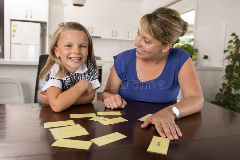 Lovely sweet and happy 6 years old daughter learning reading with flash card words game at home kitchen playing with her young bea stock photography