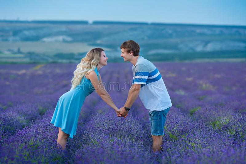 Lovely teen couple wearing blue clothes holding each other by hands while standing on a field of lavender flowers. Tender scene of. Love between two genders stock photo