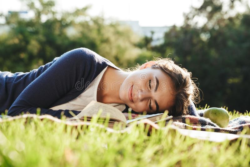 Lovely teenae girl laying on a grass outdoors stock photos