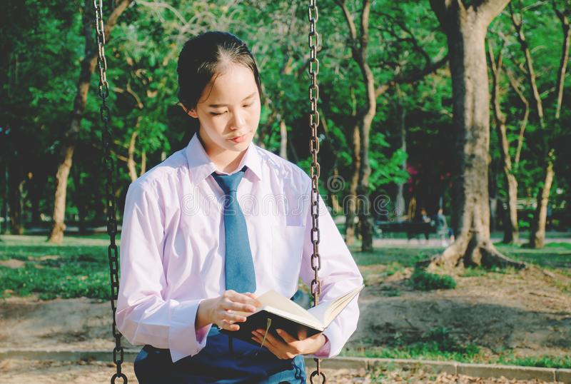 Lovely teenage girl wearing school uniform reading book while sitting on a swing at the park royalty free stock image