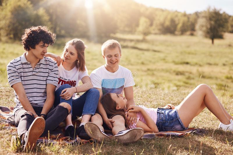 Lovely teenagers in love express mutual feeling, have positive expressions, picnic outdoor, sit on plaid, enjoys sun and green gra royalty free stock images