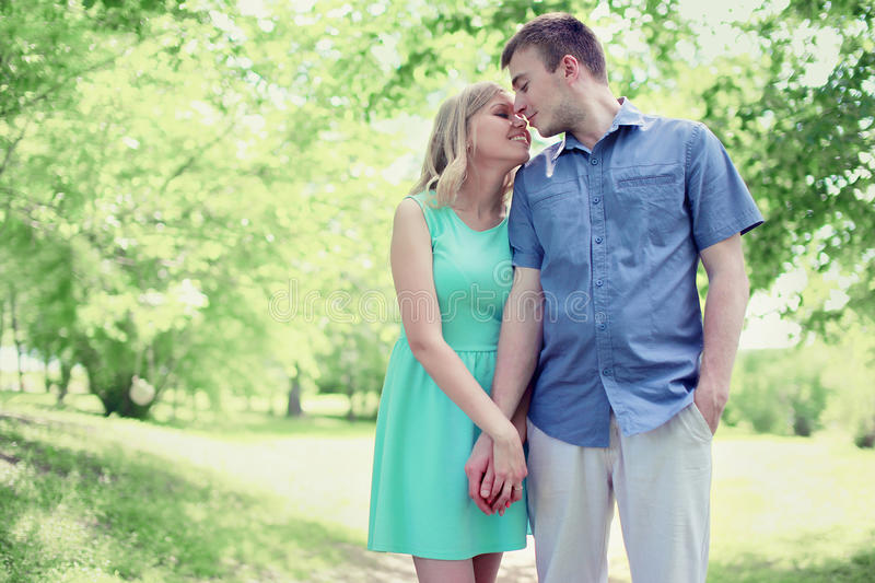 Lovely tender young couple in love walking in sunny spring park. Soft colors stock photography