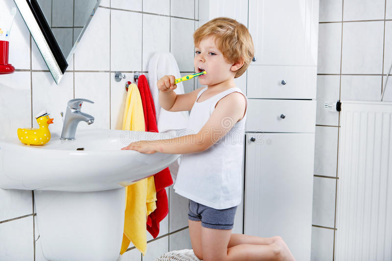 Lovely toddler boy brushing his teeth, indoors stock images