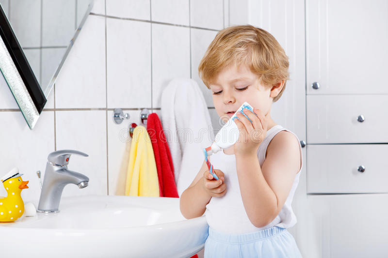 Lovely toddler boy brushing his teeth, indoors. Happy toddler boy learning brushing his teeth in domestic bath. Children learning how to stay healthy royalty free stock images