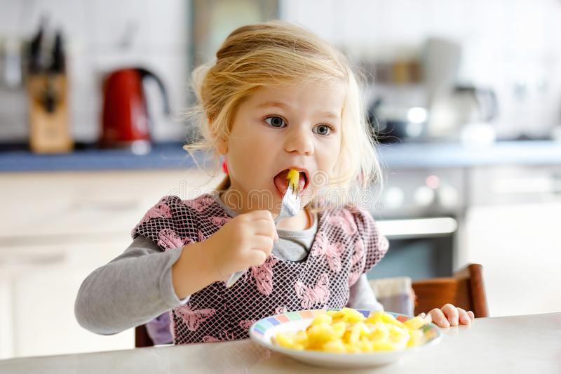 Lovely toddler girl eating healthy fried potatoes for lunch. Cute happy baby child in colorful clothes sitting in royalty free stock photography