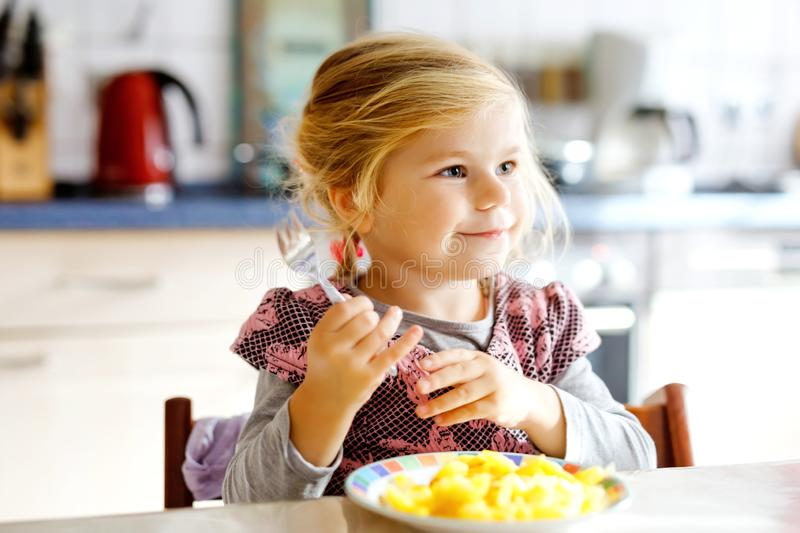 Lovely toddler girl eating healthy fried potatoes for lunch. Cute happy baby child in colorful clothes sitting in royalty free stock photos