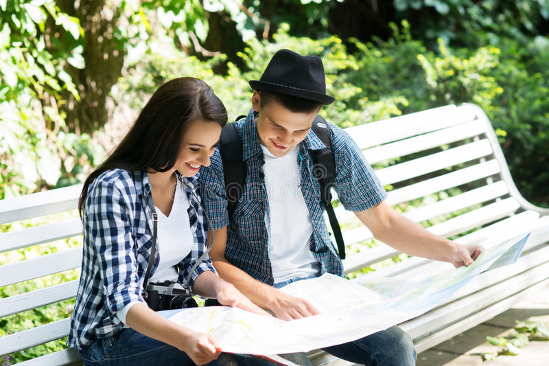 Lovely tourist couple checking the map. Young travelling couple checking out the map in the park stock images