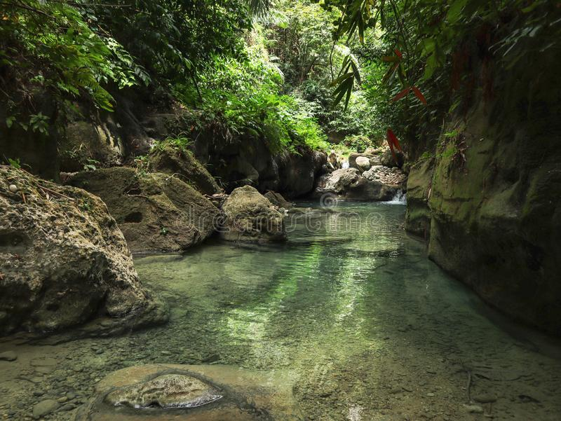 Lovely travel couple at Tropical Waterfall in the jungle in Dao Falls in Cebu Island, Philippines. Couple relaxing on the green canyon road at the middle of stock photos
