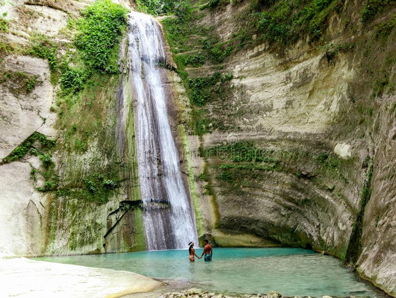 Lovely travel couple at Tropical Waterfall in the jungle in Dao Falls in Cebu Island, Philippines. Couple relaxing on the green canyon road at the middle of stock images