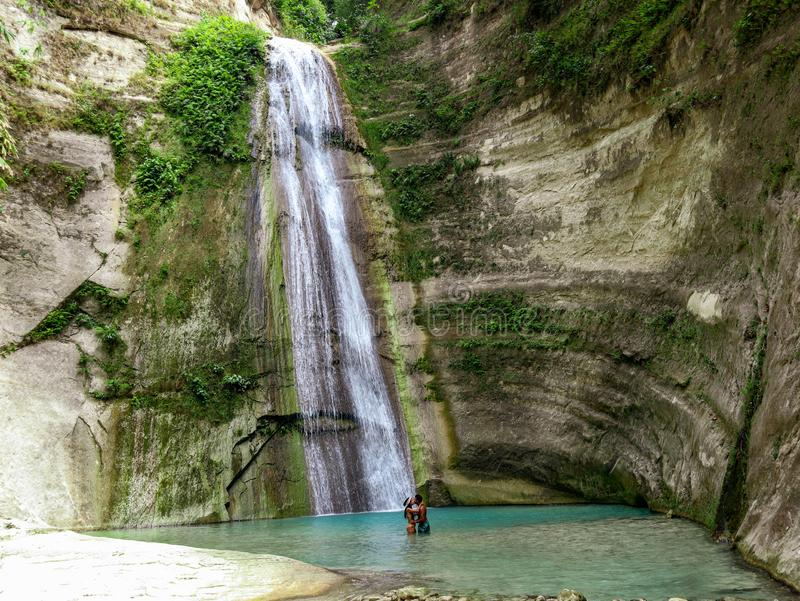 Lovely travel couple at Tropical Waterfall in the jungle in Dao Falls in Cebu Island, Philippines. Couple relaxing on the green canyon road at the middle of stock image